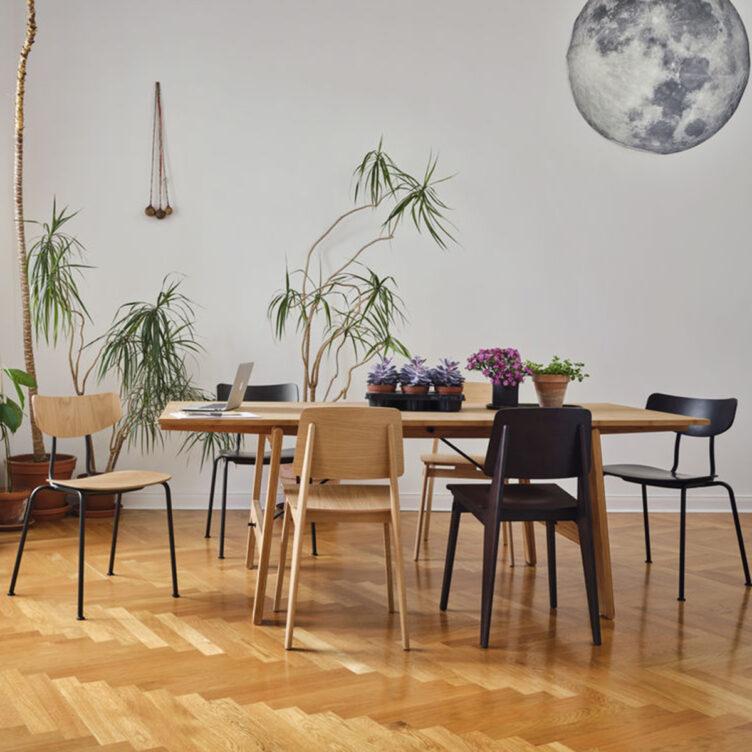 Sitzgruppe mit verschiedenen Vitra Stühlen.Der Vitra Stuhl Chaise Tout Bois basiert auf dem ikonischen Entwurf des Standard SP von Jean Prouvé